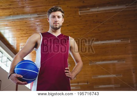 Portrait of male basketball player with hand on hip standing in court