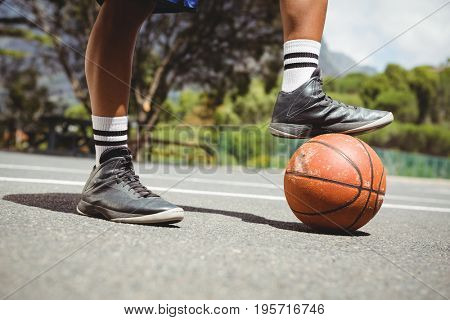 Close up of man standing with one leg on basketball at court