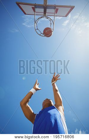 Directly below shot of male teenager playing basketball against sky on sunny day