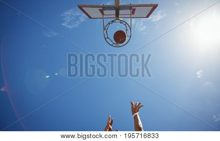 Directly below shot of person playing basketball against sky on sunny day