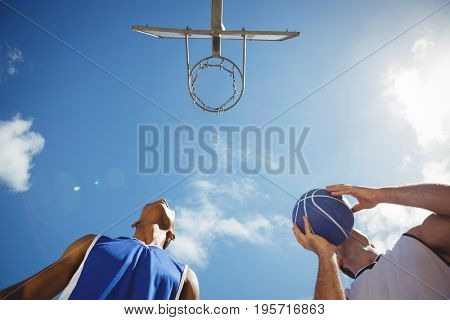 Low angle view basketball players practicing in court against sky on sunny day