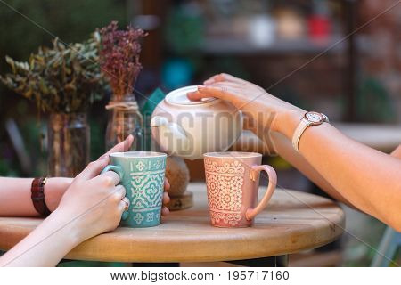female pouring tea in cup in morning cafe