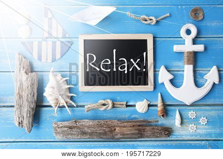 Flat Lay Of Chalkboard On Blue Wooden Background. Sunny Nautic Or Maritime Summer Decoration As Holiday Greeting Card. English Text Relax