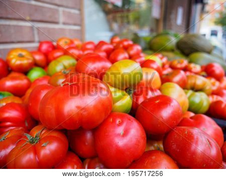 Close-up detail of a stack of ripe Dutchman organic tomatoes on sale at a local farmer's market. Valencia Spain. Travel and food concept.