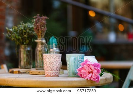 Cups Of Tea And Peony On Wooden Table In Street Cafe