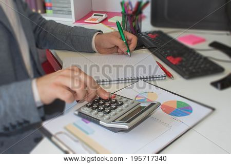 Close up young man with calculator counting making notes at home hand is writing in a notebook. Savings finances concept