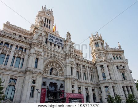 June 21 2017. Wide-angle view of Palacio de Cibeles the old city council with a sign welcoming refugees. Madrid Spain. Travel and politics editorial concept.