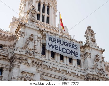June 21 2017. Close-up of a sign welcoming refugees next to the Spanish flag on the facade of Palacio de Cibeles Madrid Spain. Travel and politics editorial concept.