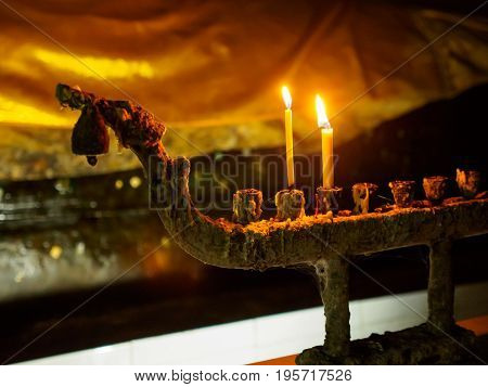 Close-up detail of two candles lit on an old candle holder in front of a statue of the reclining Buddha covered with a yellow shrould. Jompon cave Ratchaburi Thailand. Travel and religion concept.