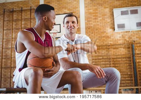 Basketball player doing fist bump with coach while sitting on bench in court