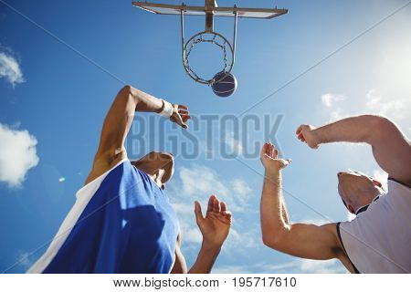 Low angle view of friends playing basketball in court against sky