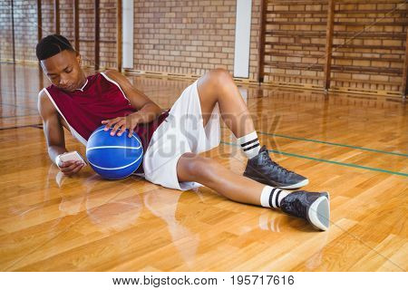 Full length male basketball player using mobile phone while reclining on floor in court