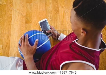 Overhead view of male basketball player using mobile phone while reclining on floor in court
