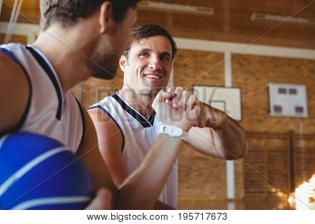 Smiling basketball players doing fist bump while sitting on bench in court