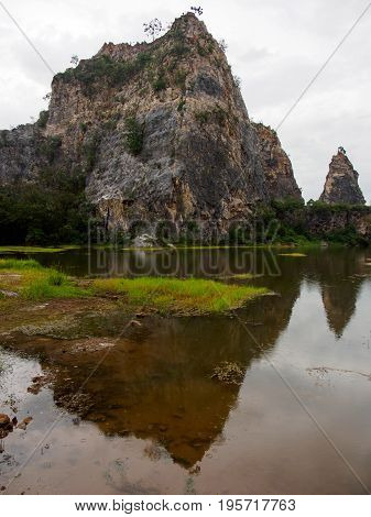 Wide angle view of the craggy mountains of Khao Ngu Stone Park and their reflections in the shallow lakes during a rainy day. Vertical orientation. Ratchaburi Thailand. Travel and nature concept.