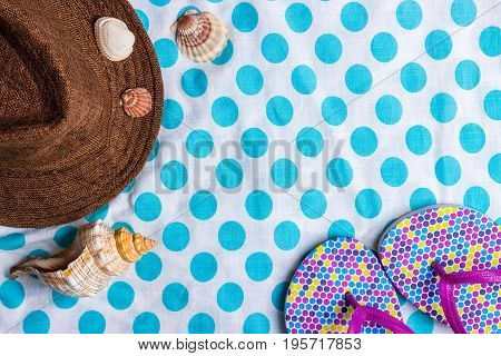 Summer holiday setting with flip-flops Seashells and straw hat