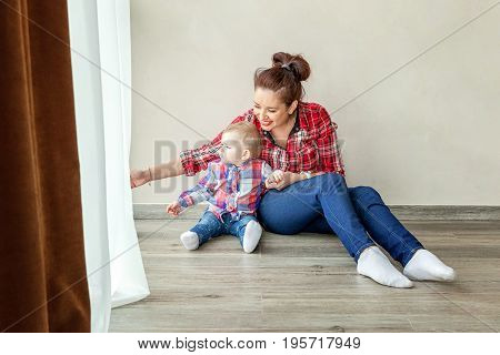 Young mother holding her young daughter. Woman and new born girl relax in a bedroom near the windiow. . Mother breast feeding baby. Family at home.