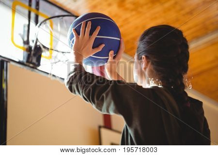 Side view of young woman practicing basketball while standing in court