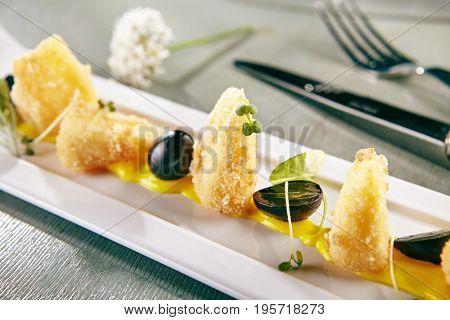 Restaurant Hot Starter Food - Deep Fried Camembert with Mango Sauce. Gourmet Restaurant Appetizers Menu. Deep Fried Camembert Served with Grapes and Greens