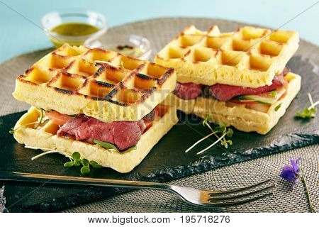 Restaurant Hot Starter Food - Rare Beef Waffle Sandwich. Gourmet Restaurant Appetizers Menu. Rare Beef Waffle Sandwich Served with Greens and Vegetables
