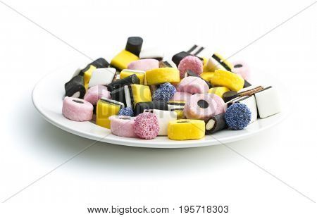 Mixed liquorice candies on plate isolated on white background.