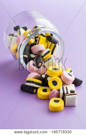 Mixed liquorice candies on colorful background.
