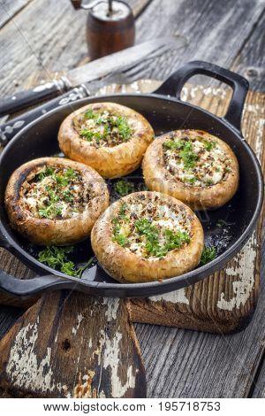 Traditional Italian Mushroom Caps stuffed with Feta as close-up in a rustic frying pan