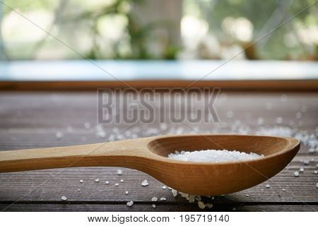 Sea Salt In A Wooden Spoon On A Table, Side View