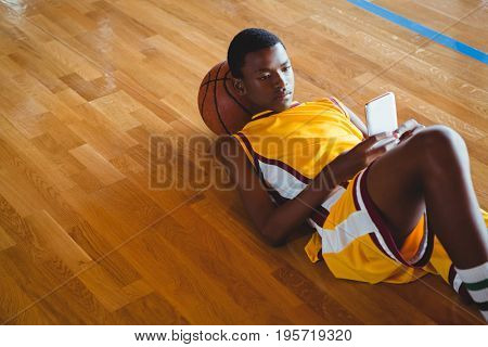 High angle view of male teenager using mobile phone while lying on floor