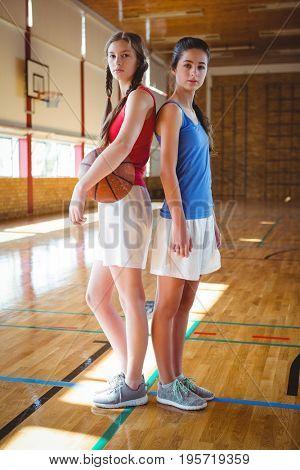 Full length of female basketball players standing back to back