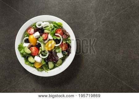 fresh greek salad in plate on stone table