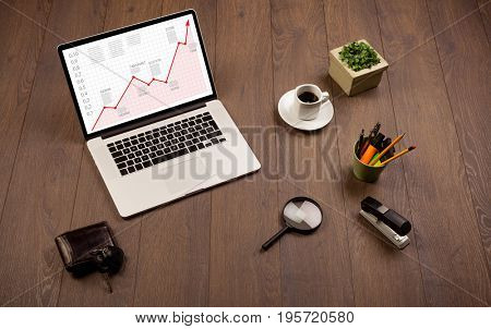 Computer wooden desk with laptop and red arrow chart in screen