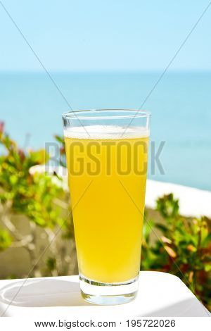 closeup of a glass with refreshing spanish clara, beer mixed with lemonade, on a table, with the ocean in the background