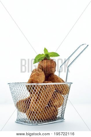 some homemade croquetas, spanish croquettes, served in a metal basket, on a white background, with a negative space on top