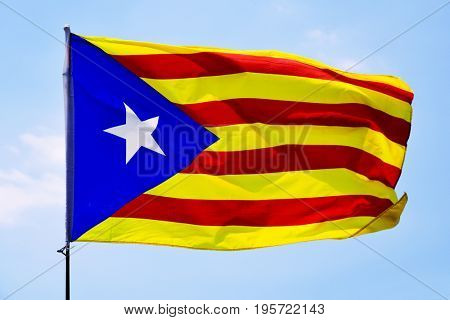 the estelada, the catalan pro-independence flag, waving on the blue sky