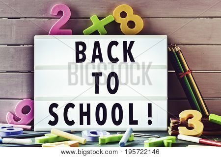 the text back to school in a lightbox placed against a rustic wooden background, surrounded by three-dimensional numbers and chalks and pencil crayons of different colors
