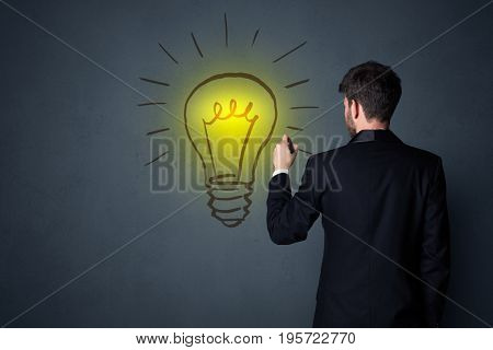 Young businessman in black suit standing in front of a drawn yellow lightbulb