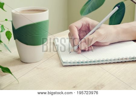 The hand of a woman with a pencil is written in a diary with spirals. Beside to the table is a cup of coffee and plant with green leaves. Side view
