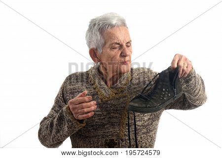 A senior woman smelling a shoe on white background