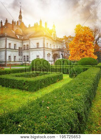 ancient castle in autumn. green lawn. Dramatic sky