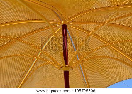Golden metal parasol umbrella for ultraviolet light protection and sunshade on hot summer days