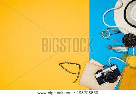 Travel accessories top view on colorful background with copy space. Lay flat woman traveler products on blue and yellow seamless