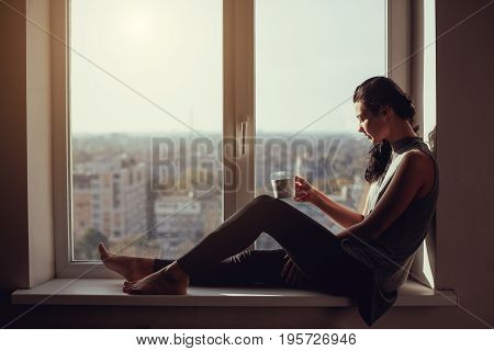 Resting and thinking woman. Calm girl with cup of tea or coffee sitting on the window-sill at home. Side view. Young attractive multi-racial Asian Caucasian lady in casual clothes resting indoors