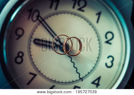 Wedding rings and alarm clock, happiness and love