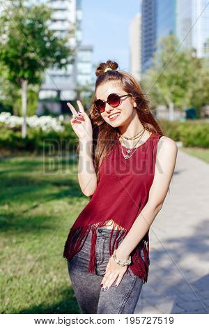 Portrait of beautiful sexy slim smiling white Caucasian girl woman with long red hair wearing jeans and t-shirt with sunglasses. Girl having fun showing victory sign. Urban street fashion style.