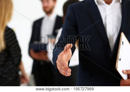 Businessman offer hand to shake as hello in office closeup. Serious business friendly support service excellent prospect introduction or thanks gesture gratitude invite to participate concept