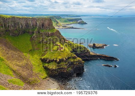 view on Amphitheatre, Port Reostan Bay and Port Noffer Bay with Giant's Causeway on background, County Antrim, Northern Ireland, UK