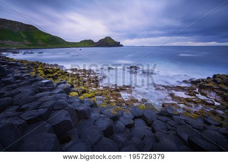 sunset over basalt rocks formation Giant's Causeway, Port Ganny Bay and Great Stookan, County Antrim, Northern Ireland, UK