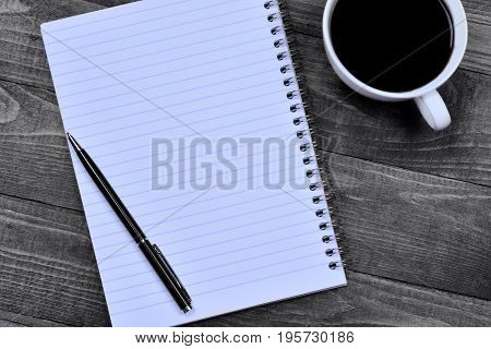 Empty notepad with pen and coffee cup on wooden table