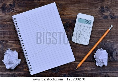 Notebook with pencil and calculator on wooden table